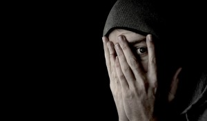 man covering face looking through fingers black background with copy space